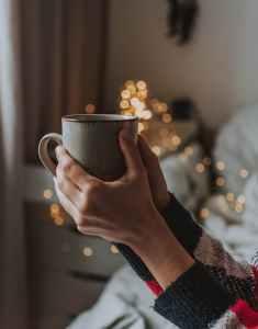 person holding gray mug